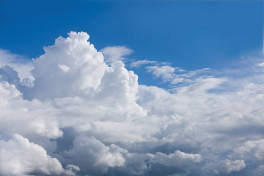 Puffy clouds in sunny, blue sky : Stock Photo