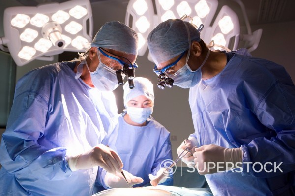 Stock Photo: 4208R-11188 Concentrating surgeons performing operation in operating room