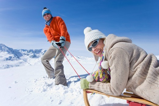 Man puling wife through snow on sled : Stock Photo