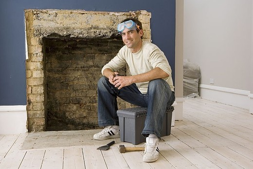 Man with safety goggles doing DIY at home, sitting on toolbox beside fireplace, smiling, portrait : Stock Photo