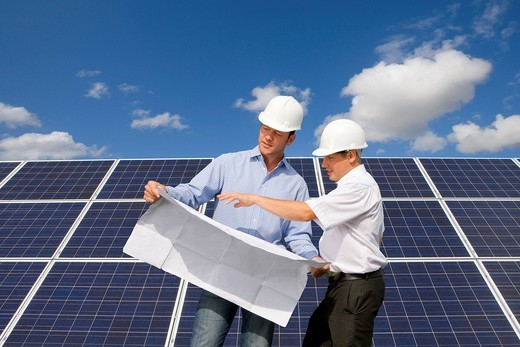 Technicians holding blueprints talking near large solar panels : Stock Photo