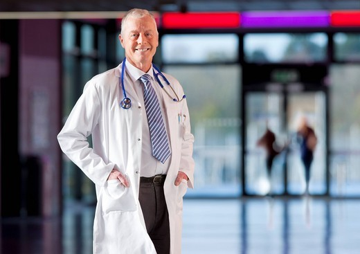 Stock Photo: 4208R-11312 Smiling doctor in lab coat standing in hospital hallway