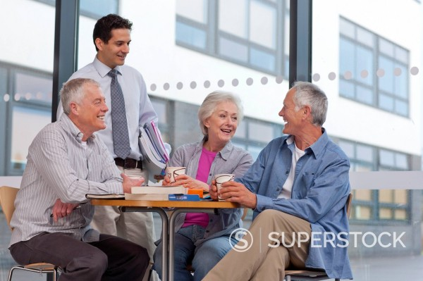 Adult students and teacher taking coffee break talking about college : Stock Photo