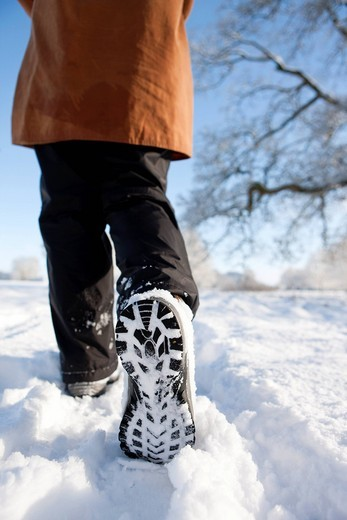Close up of woman´s feet walking through field of snow : Stock Photo