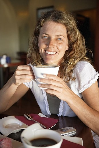 Stock Photo: 4208R-11370 Young woman drinking cup of coffee in cafe, smiling, portrait
