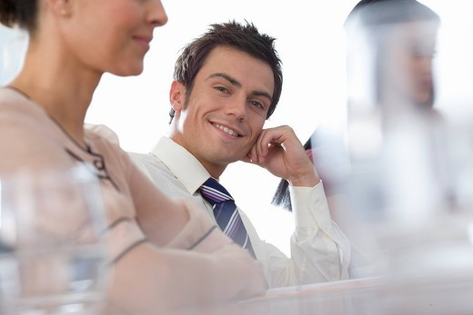 Stock Photo: 4208R-1138 Businessman and women at table in meeting, portrait of man smiling differential focus