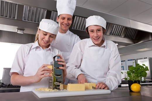 Chef watching trainees grate and slice cheese in commercial kitchen : Stock Photo