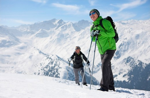 Couple hiking on mountain top in snow : Stock Photo