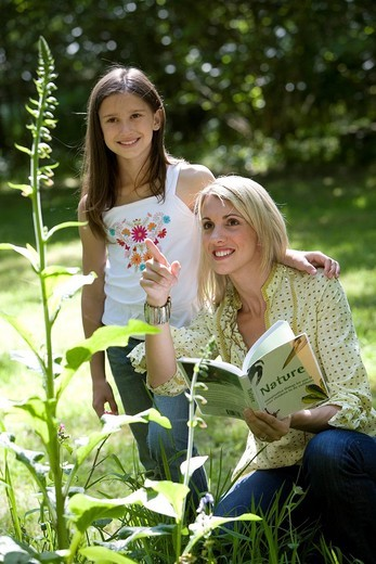Stock Photo: 4208R-1182 30´s mother with nature book pointing to plant with 8 year old daughter in countryside,