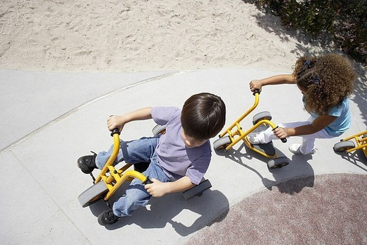 Boy and girl 4-6 riding toy tricycle and push scooter in playground, overhead view tilt : Stock Photo