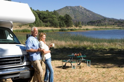 Mature couple with mugs by motor home by lake, side view : Stock Photo