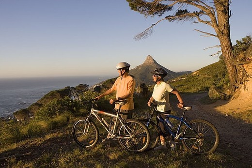 Mature couple standing with bicycles on mountain trail, looking at Atlantic Ocean horizon, side view : Stock Photo