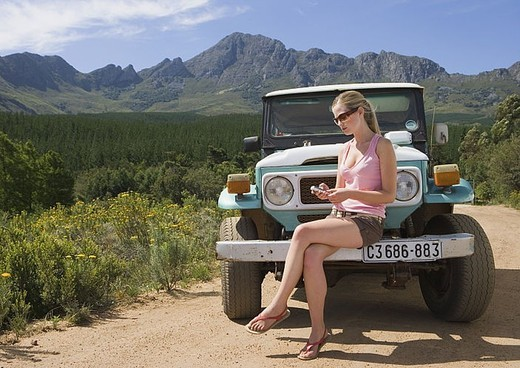 Young woman sitting on bumper of parked jeep on dirt track in rural setting, using mobile phone : Stock Photo