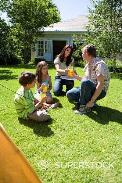 Family taking break from assembling tent on garden lawn, mother serving orange juice, smiling : Stock Photo