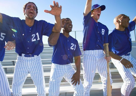 Excited baseball team jumping up from bench in stand during competitive baseball game, cheering, front view backlit : Stock Photo