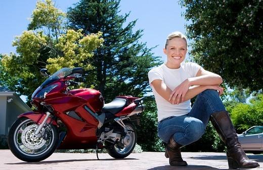 Woman crouching near red motorbike on driveway, smiling, portrait surface level : Stock Photo