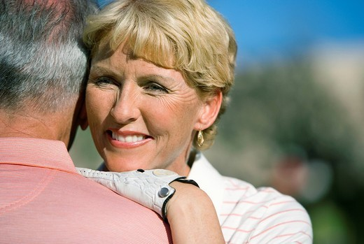 Mature couple embracing on golf course, focus on woman wearing golf glove, smiling, close-up, view over shoulder : Stock Photo