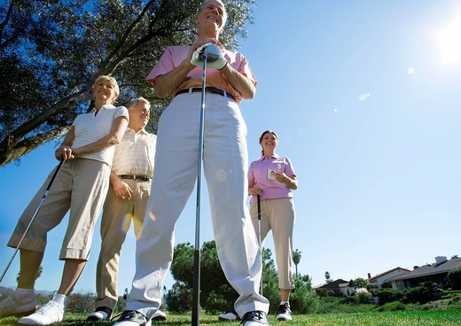 Stock Photo: 4208R-12680 Two mature couples standing on golf course, smiling, front view, portrait surface level, lens flare