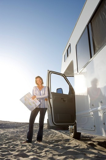 Mature woman with map by motor home on beach, low angle view lens flare : Stock Photo