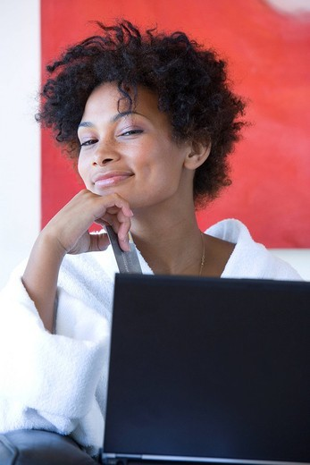 Young woman holding credit card by laptop, smiling : Stock Photo
