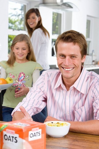 Man eating breakfast at table, smiling, portrait, family in background : Stock Photo