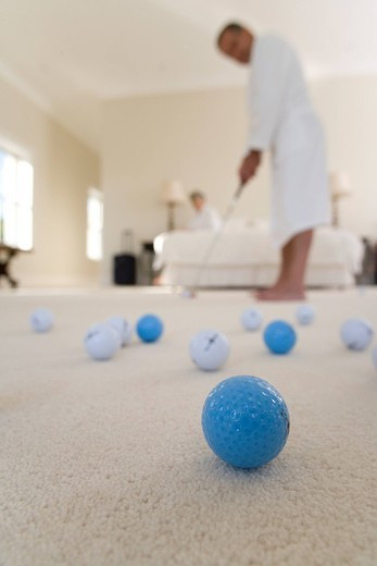 Stock Photo: 4208R-12979 Senior couple in bedroom, man practising golf putt, focus on golf balls in foreground