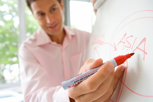 Stock Photo: 4208R-13086 Young man writing on whiteboard, focus on hand