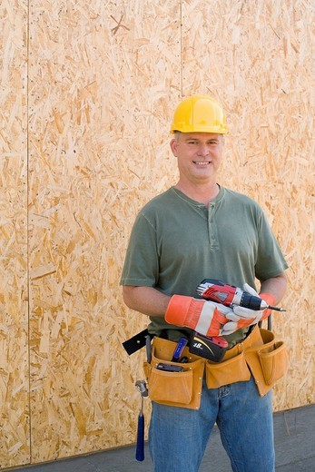 Male builder in hardhat with electric drill, smiling, portrait : Stock Photo
