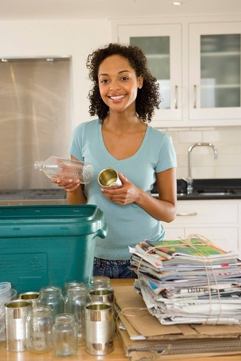 Young woman putting glass bottle and can into recycling bin in kitchen, smiling, portrait : Stock Photo