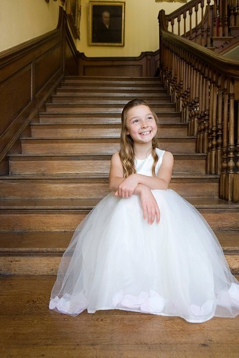 Stock Photo: 4208R-13292 Flower girl 10-12 on stairs, smiling, low angle view