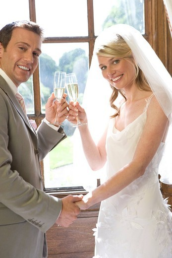 Bride and groom toasting with champagne, smiling, portrait, side view : Stock Photo