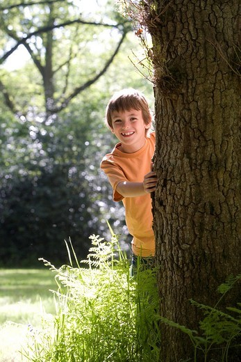 Boy 8-10 peeking out from behind tree, smiling, portrait : Stock Photo