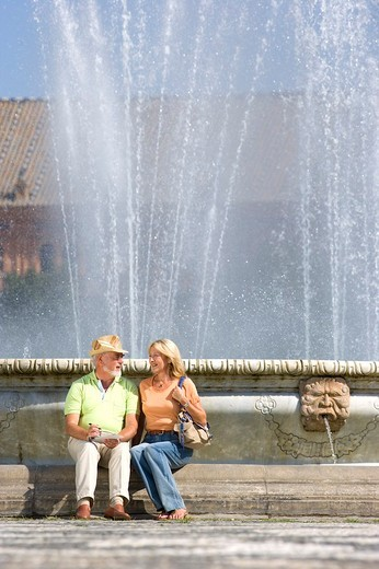 Senior couple sitting by fountain : Stock Photo