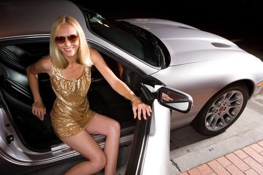 Stock Photo: 4208R-1334 Young woman alighting from car at night, elevated view