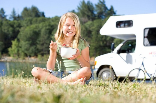 Girl 9-11 eating from bowl on grass with legs crossed, motor home in background, smiling, portrait : Stock Photo