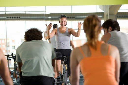 Fitness instructor leading class on exercise bicycles in gym, rear view : Stock Photo