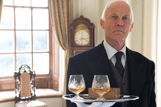 Butler with tray of drinks, portrait, close-up : Stock Photo