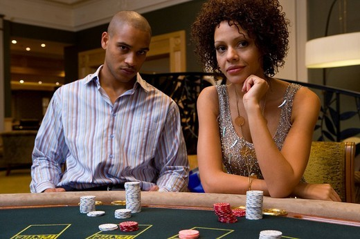 Stock Photo: 4208R-13764 Young man and woman gambling at poker table, portrait