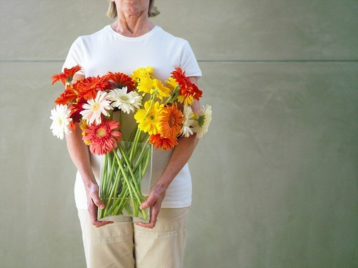 Woman with vase of flowers, mid section : Stock Photo