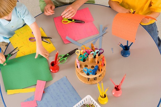 Pre-school children 3-5 at nursery with scissors and coloured paper at table, elevated view : Stock Photo