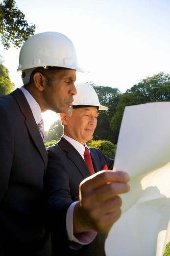 Businessman and colleague in hardhats looking at blueprint, low angle view : Stock Photo