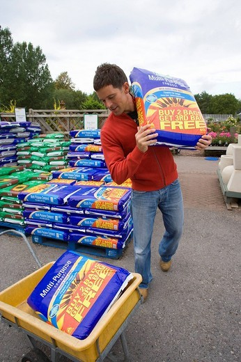 Stock Photo: 4208R-13944 Man in garden shop with bag of soil