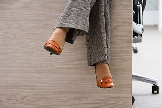 Stock Photo: 4208R-14191 Businesswoman wearing checked grey trousers and orange high heels, sitting on desk in office, low section