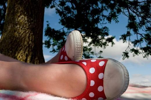 Girl relaxing under tree : Stock Photo