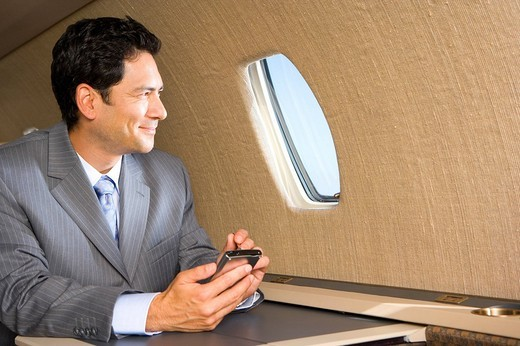 Businessman with electronic organiser on aeroplane, looking out window, close_up : Stock Photo