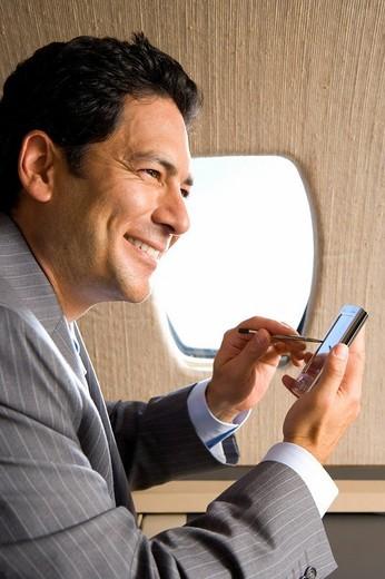 Businessman using electronic organiser on aeroplane, smiling, close_up : Stock Photo