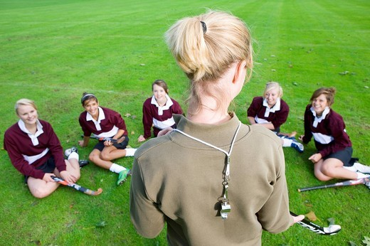 Stock Photo: 4208R-14409 Coach standing before teenage girl field hockey team