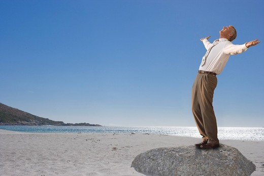 Businessman standing on beach with arms outstretched : Stock Photo