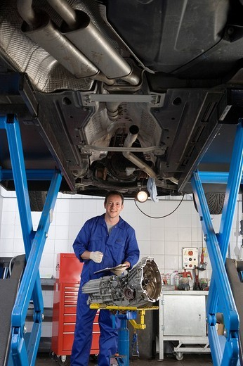 Stock Photo: 4208R-1460 Mechanic with clipboard and part by elevated car, portrait, low angle view
