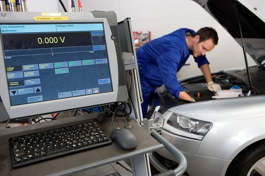 Mechanic working on car by computer : Stock Photo